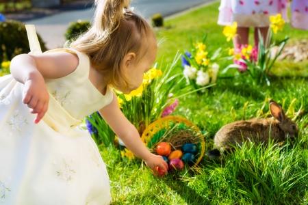pascuas navide�as: Ni�os en una caza del huevo de Pascua en un prado en primavera, en primer plano la vida Conejo de Pascua y est� esperando una ni�a encuentra los huevos de Pascua
