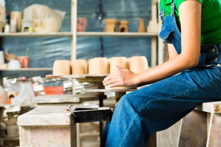 alfarero: Mujer Potter creaci�n de un taz�n en un torno de alfarero