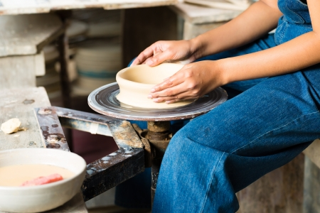 potters wheel: Female Potter creating a bowl on a Potters wheel Stock Photo