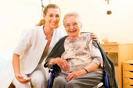 nursing homes: Young nurse and female senior in nursing home, the old lady sitting in a wheel chair Stock Photo