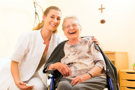 helping people: Young nurse and female senior in nursing home, the old lady sitting in a wheel chair Stock Photo