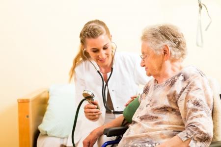 servicios publicos: Enfermera joven y mujer mayor en hogar de ancianos, la presión arterial se va a medir