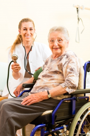 public welfare: Young nurse and female senior in nursing home, the blood pressure is going to be measured Stock Photo