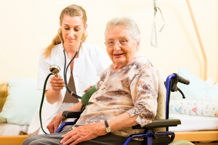 Young nurse and female senior in nursing home, the blood pressure is going to be measured Stock Photo