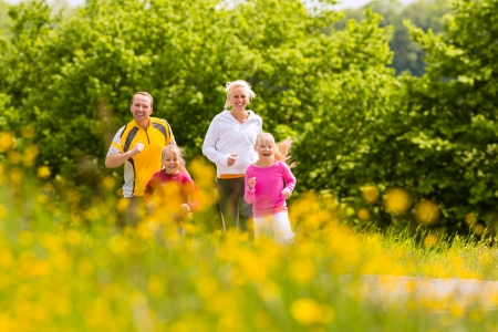 family fitness: Happy Family with two girls running or jogging for sport and better fitness in a meadow in summer