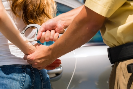 Police officer arresting a woman with handcuffs Stock Photo - 18230956