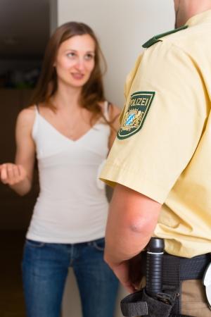 zeugnis: Polizist vor der Haust�r des Hauses Abfrage eine Frau oder Zeugen �ber eine polizeiliche Untersuchung