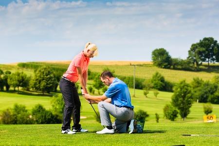 골프 프로와 연습장에서 젊은 여성 골프 선수, 그녀는 아마도 운동을한다