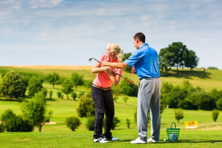 Young female golf player at Driving Range with a Golf Pro, she presumably does exercise photo