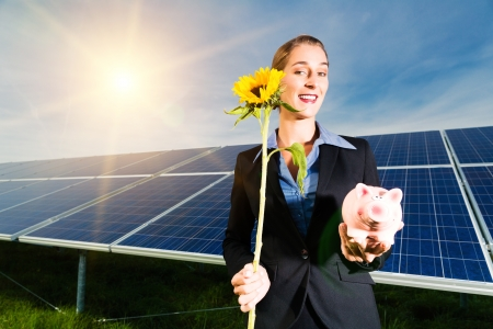 lucrative: Photovoltaic system with solar panels for the production of renewable energy through solar energy, the investor is in front with a piggybank and a sunflower