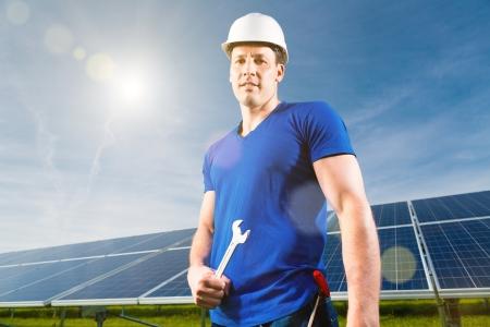 Impianto fotovoltaico con pannelli solari per la produzione di energia rinnovabile attraverso l'energia solare, un tecnico o lavoratore in piedi nella parte anteriore
