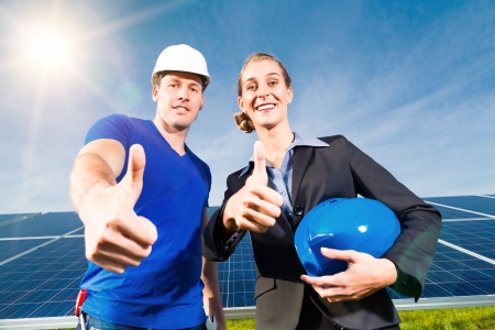 voltaic: Photovoltaic system with solar panels for the production of renewable energy through solar energy, a technician or worker and the investor or owner standing in front