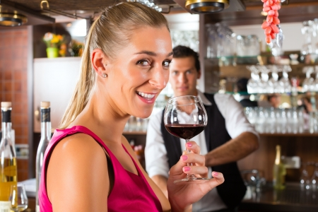 Woman holding a glass of red wine in hand at the bar of hotel or restaurant and smiling photo