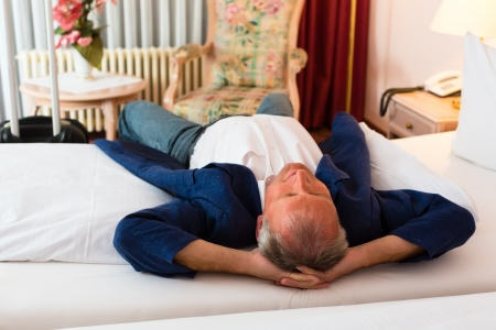 Senior man lying on the bed in the hotel room and relaxing Stock Photo - 18231100
