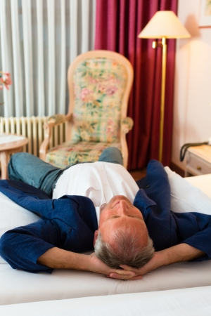 Senior man lying on the bed in the hotel room and relaxing photo