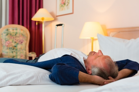 Senior man lying on the bed in the hotel room and relaxing Stock Photo - 18231144