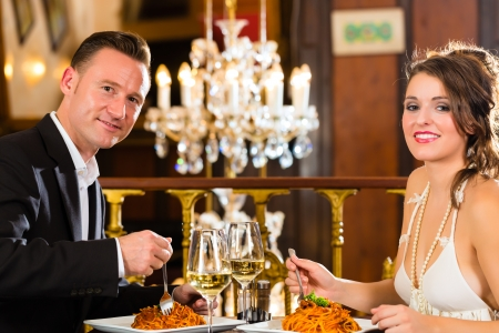 couple dining: happy couple have a romantic date in a fine dining restaurant they drink wine and clinking glasses, cheers - a large chandelier is in Background