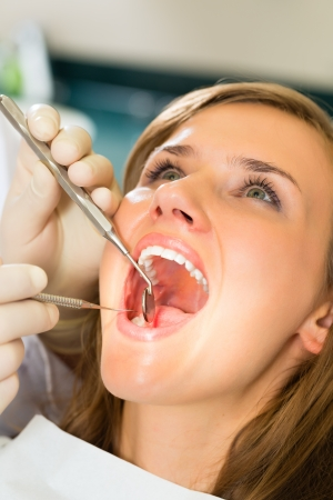 Female patient with dentist in a dental treatment, wearing gloves Stock Photo - 18231039