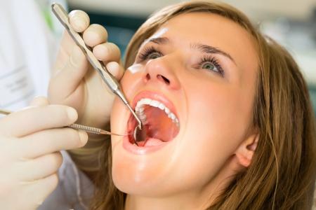 dentist s office: Pacjentka z stomatologa w leczeniu stomatologicznym, rÄ™kawiczkach Zdjęcie Seryjne