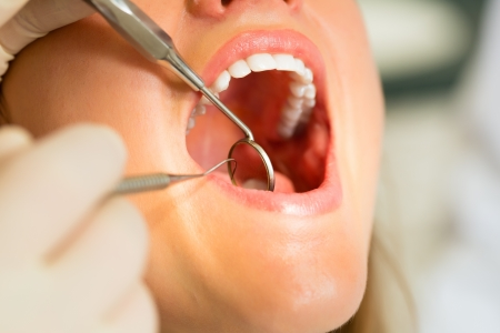 Female patient with dentist in a dental treatment, wearing gloves Stock Photo - 18231110