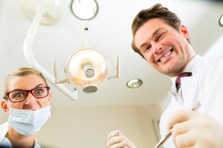 Scary dentista y asistente en un tratamiento, desde la perspectiva de un paciente