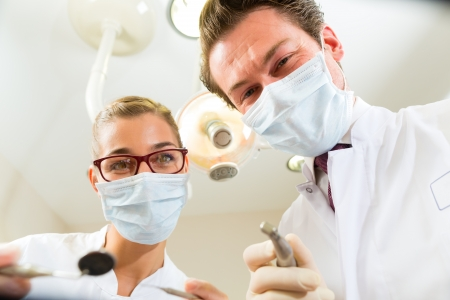 Dentist and assistant at a treatment, from the perspective of a patient photo