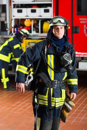 bombero de rojo: bombero joven de pie en uniforme delante del cami�n de bomberos, est� listo para su despliegue