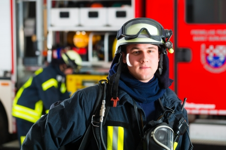 young fireman in uniform standing in front of firetruck, he is ready for deployment Stock Photo - 18230951