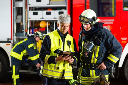 briefing: Fire brigade - Squad leader gives instructions, he used the Tablet Computer to plan the deployment Stock Photo
