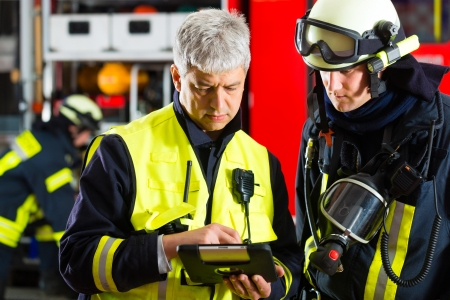 fireman helmet: Fire brigade - Squad leader gives instructions, he used the Tablet Computer to plan the deployment Stock Photo