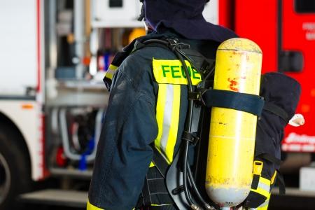 bombero de rojo: bombero joven de pie en uniforme delante del camión de bomberos, está listo para su despliegue