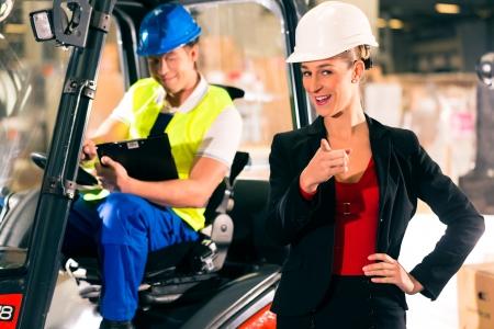 forwarding: Carretilla elevadora con portapapeles en el almac�n de la empresa de transporte de carga, visor s�per femenina o expedidor apuntando al espectador