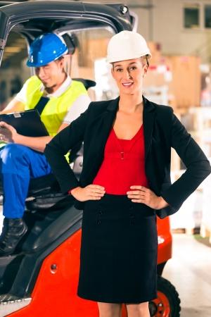forwarding: Carretilla elevadora con portapapeles en el almac�n de la empresa de transporte de carga, visor s�per femenina o expedidor mirando al espectador