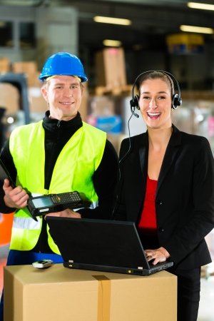 Teamwork - warehouseman or forklift driver and female supervisor with laptop, headset and cell phone, at warehouse of freight forwarding company - a forklift is in Background Stock Photo - 18231139
