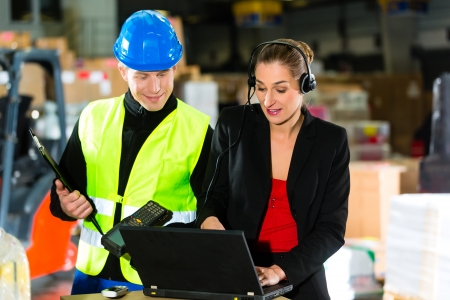 Teamwork - warehouseman or forklift driver and female supervisor with laptop, headset and cell phone, at warehouse of freight forwarding company - a forklift is in Background Stock Photo - 18231036