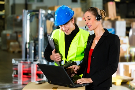 Teamwork - warehouseman or forklift driver and female supervisor with laptop, headset and cell phone, at warehouse of freight forwarding company - a forklift is in Background photo