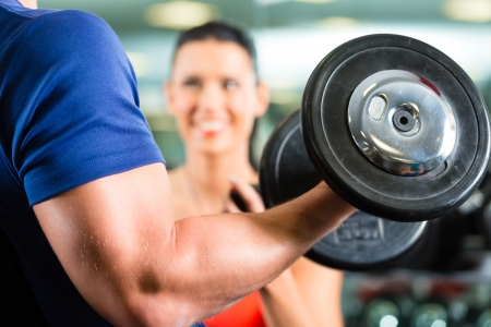 Man or Bodybuilder with his personal fitness trainer in the gym exercising sport with dumbbells, closeup photo