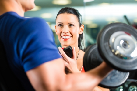 Man or Bodybuilder with his personal fitness trainer in the gym exercising sport with dumbbells, closeup Stock Photo - 18231088