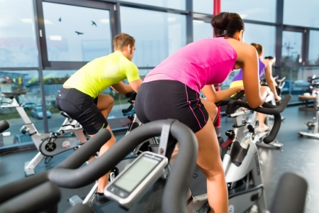Young People - group of women and men - doing sport Spinning in the gym for fitness Stock Photo - 18231048