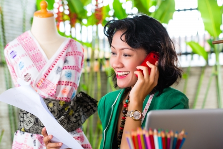 customer tailor: Freelancer - Fashion designer working at home on a design or draft, she uses a mobile phone, to talk with a client