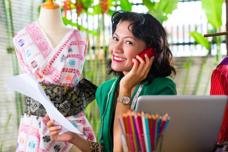 Freelancer - Fashion designer working at home on a design or draft, she uses a mobile phone, to talk with a client Stock Photo - 18230965