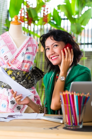 freelancer: Freelancer - Fashion designer working at home on a design or draft, she uses a mobile phone, to talk with a client