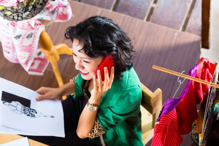 telecommuter: Freelancer - Fashion designer working at home on a design or draft, she uses a mobile phone, to talk with a client