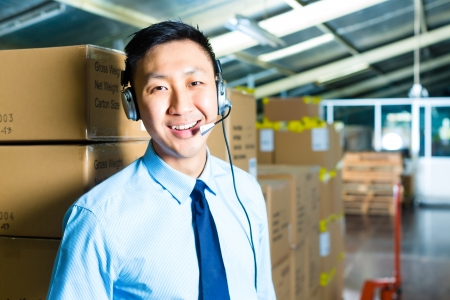 warehouse worker: Young man in a suit with a headset in a warehouse, he is from the Customer Service
