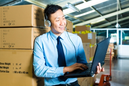 efficiently: Young man in a suit with headset and laptop in a warehouse, he is from the Customer Service