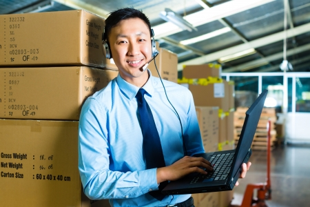 freight: Young man in a suit with headset and laptop in a warehouse, he is from the Customer Service
