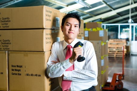 barcode scanner: Young man in a suit with a bar code scanner in a warehouse