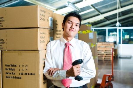 efficiently: Young man in a suit with a bar code scanner in a warehouse