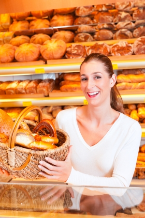 bakery products: Female baker or saleswoman in her bakery with fresh pastries and bakery products
