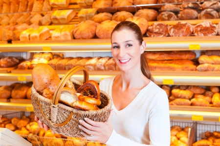 pastry shop: Female baker or saleswoman in her bakery with fresh pastries and bakery products